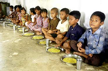 Children eat food at an anganwadi centre in Kutnabari village in Tripura