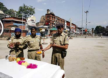 Policemen pray as they place offerings on top of their vehicles during a curfew in Srinagar
