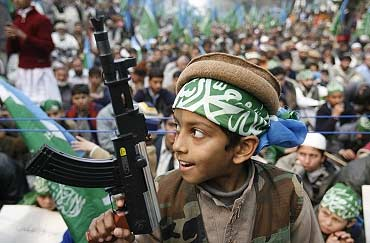 A boy holds a toy gun during an anti-India rally