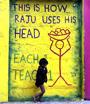 A child walks past graffiti on a street side wall in Mumbai