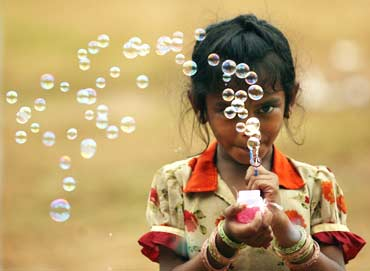 A girl blows bubbles to attract buyers