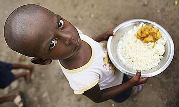 A student holds his free mid-day meal in a primary school