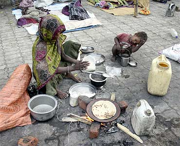 A homeless woman prepares roti on a footpath as a child looks on