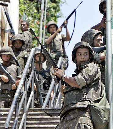 Brazilian soldiers take position during an operation against drug gangs in a Rio de Janeiro slum