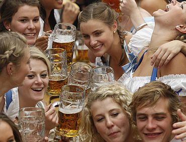 People wearing traditional Bavarian clothes toast with beer during the opening day of the 177th Oktoberfest in Munich
