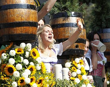 People in traditional Bavarian clothes take part in the Parade of the Landlords and Breweries during the opening of the 177th Oktoberfest in Munich