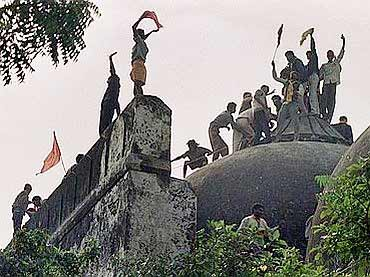 'Kar Sevaks' stand atop the demolished Babri Masjid