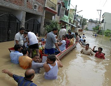 Residents travel by boat on a flooded street after heavy monsoon rains in Moradabad