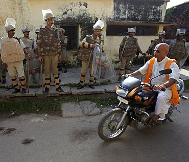 A priest rides a motorcycle as policemen stand guard on a street in Ayodhya