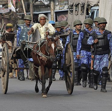 Rapid Action Forces personnel patrol a road as a man on a horse cart passes by in Ayodhya