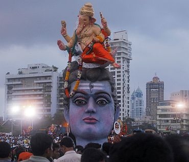 Devotees watch idols of Ganesha and Lord Shiva as they are placed on the seashore before immersion