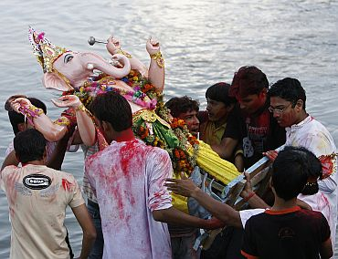 Devotees immerse an idol of Lord Ganesha