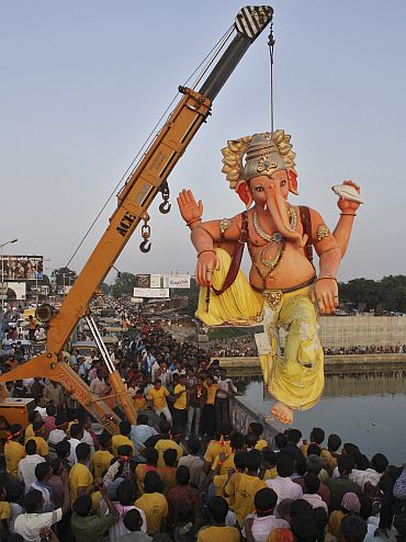 A crane lowers a Ganesh idol for immersion in river Sabarmati