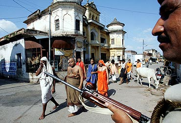Pilgrims walk towards the Ram temple as a policeman stands guard in Ayodhya