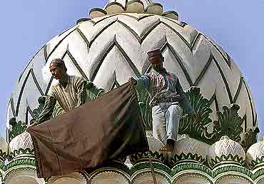 Muslims hoist a black flag atop a mosque in Ayodhya