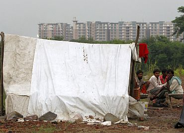 Local residents living on the banks of river Yamuna are pictured outside their makeshift tent in front of the athletes village of the 2010 Commonwealth Games in New Delhi