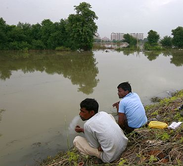 Local residents living on the banks of river Yamuna are pictured near the athletes village of the 2010 Commonwealth Games in New Delhi