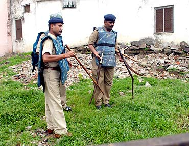 City Superintendent of Police, Ratlam,  Mahendra Tarnekar, right, inspects swords recovered