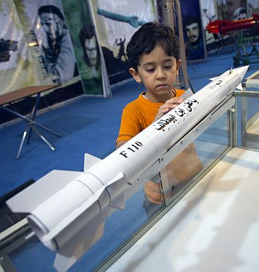 A boy looks at a model of an Iranian third-generation Fateh-110 (Conqueror) surface-to-surface missile while visiting a war exhibition held by Iran's Basij militia and revolutionary guard to mark the anniversary of the Iran-Iraq war (1980-88) on September 23