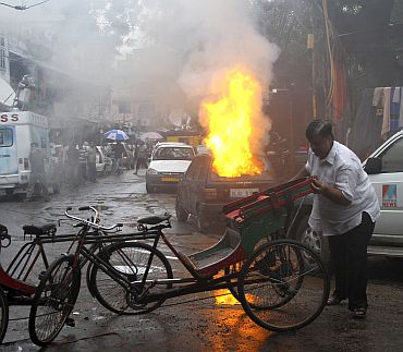 A man removes rickshaws near the car which burst into flames near the scene