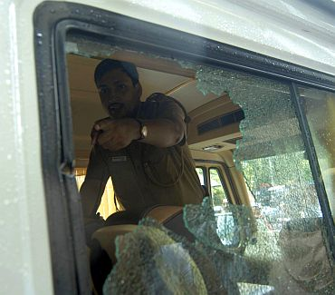 A policeman points out to the bullet mark on the window of a vehicle after the shooting incident