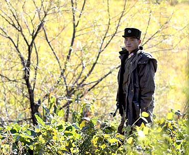 A North Korean soldier stands guard on the banks of the Yalu river near Sinuiju