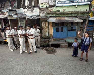 Schoolchildren wait for their school bus as policemen stand guard in Ayodhya
