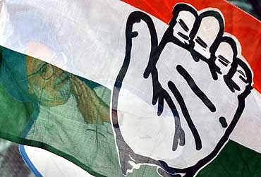 A cut out of Indian Prime Minister Manmohan Singh, seen through the Congress flag