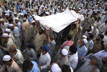 Residents carry the body of a suicide bomb victim to his grave in Peshawar