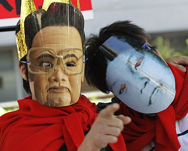 Activists wear masks depicting the North Korean leader and his son