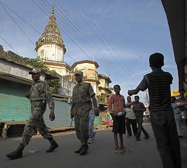 Boys fly a kite as paramilitary soldiers patrol a road in Ayodhya