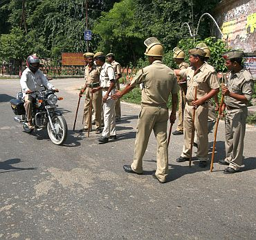 Police stop a motorbike at a checkpoint along a road in Ayodhya