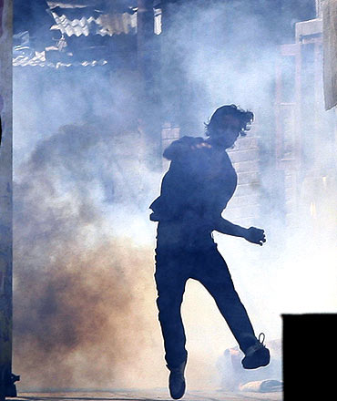 A protestor throws stones at policemen