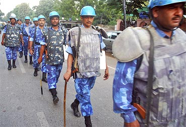 Rapid Action Force personnel patrol a road in Allahabad