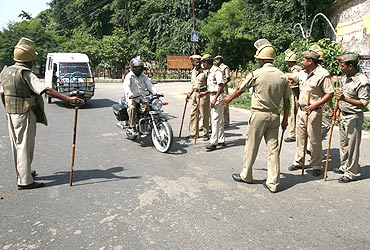 Police stop a motorbike at a checkpoint in Ayodhya