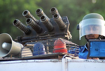 A Rapid Action Force personnel keeps guard atop his armoured vehicle in Allahabad
