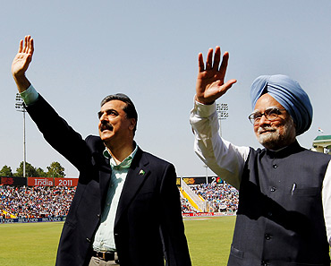 Pakistan's Prime Minister Yusuf Raza Gilani and Prime Minister Manmohan Singh wave before the  World Cup semi-final between India and Pakistan in Mohali
