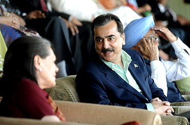 PM Gilani speaks with Congress chief Sonia Gandhi as PM Singh watches the India-Pakistan semi final at Mohali