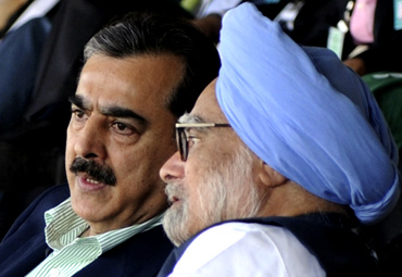 PM Singh speaks with Pakistan PM Gilani as they watch the match