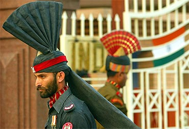 A Pakistani Patan guard and an Indian Border Security force officer march during a ceremony
