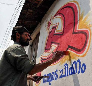 A worker gives finishing touches to a party banner on a wall