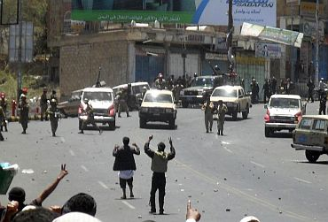 Anti-government protesters stand on a street as police and army soldiers try to disperse them during a demonstration in Taiz