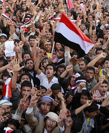 Anti-government protesters shout slogans during a sit-in in Sanaa on Monday