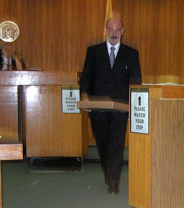 Prosecutor John Latarocca showing the guns and ammunition to the jury