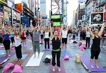 People gather to practice yoga at Times Square