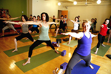 Yoga students hold a pose during an afternoon class at a yoga studio in New York