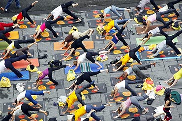 Over 200 people practice yoga at Times Square