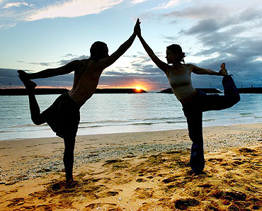 A couple practises yoga on Magic Island in Ala Moana Beach Park in Honolulu, Hawaii