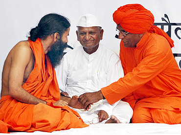 Yoga guru Swami Ramdev speaks with social activist Swami Agnivesh as Anna Hazare