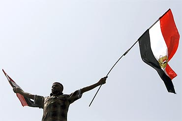 A protester waves Egyptian flags at Tahrir Square in Cairo